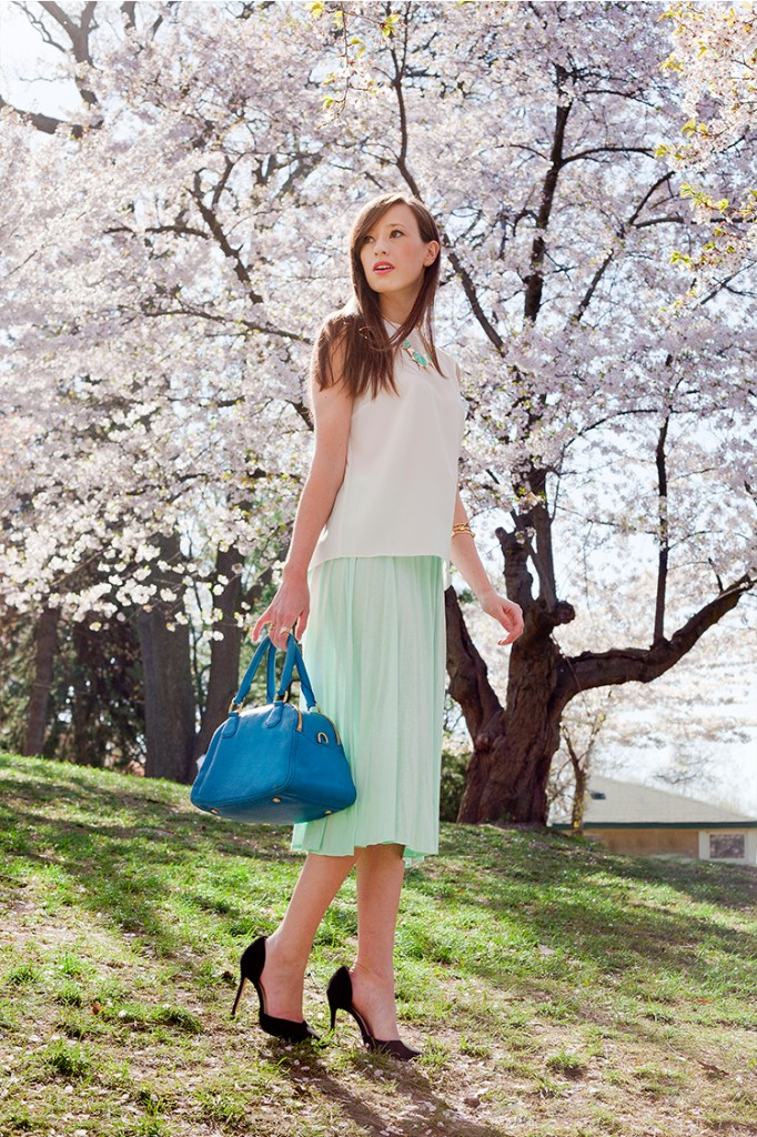 Style Bee in Green Skirt and White Shirt with a Blue Bag